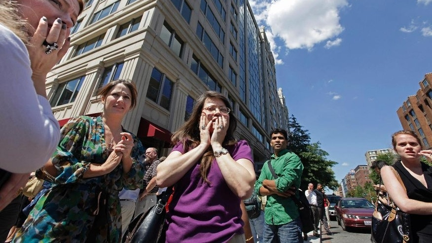 FILE - This Aug. 23, 2011 file photo shows office workers gathering on the sidewalk in downtown Washington after a 5.9 magnitude tremor shook the nation's capitol. The earthquake centered northwest of Richmond, Va., shook much of Washington, D.C., and was felt as far north as Rhode Island and New York City. A new federal earthquake risk map dials up the shaking hazard just a bit for about half of the United States and lowers it for nearly a quarter of the nation. The U.S. Geologic Survey updated Thursday its national seismic hazard maps for the first time since 2008, taking into account research from the devastating 2011 earthquake and tsunami off the Japanese coast and the surprise 2011 Virginia temblor. (AP Photo/J. Scott Applewhite, File)