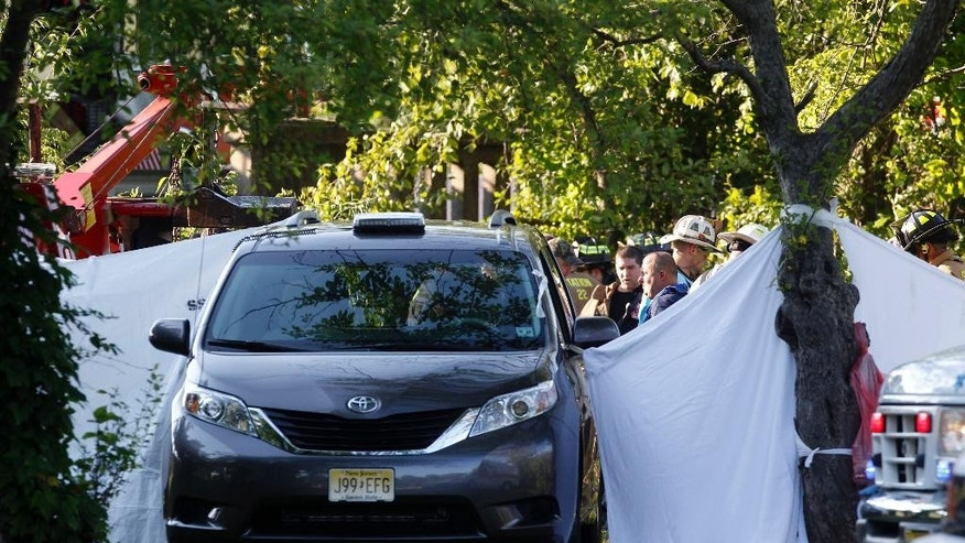 A coroners van is surrounded by privacy sheets after a collision between a dump truck and a car has sent both vehicles into a lake, submerging the car and killing its driver Thursday, July 17, 2014, in Lawrence, N.J. Lawrence police Sgt. Joe Amodio says the truck rammed the car near a traffic light Thursday afternoon and the vehicles wound up in Colonial Lake, with the truck on top of the submerged car. (AP Photo/Mel Evans)