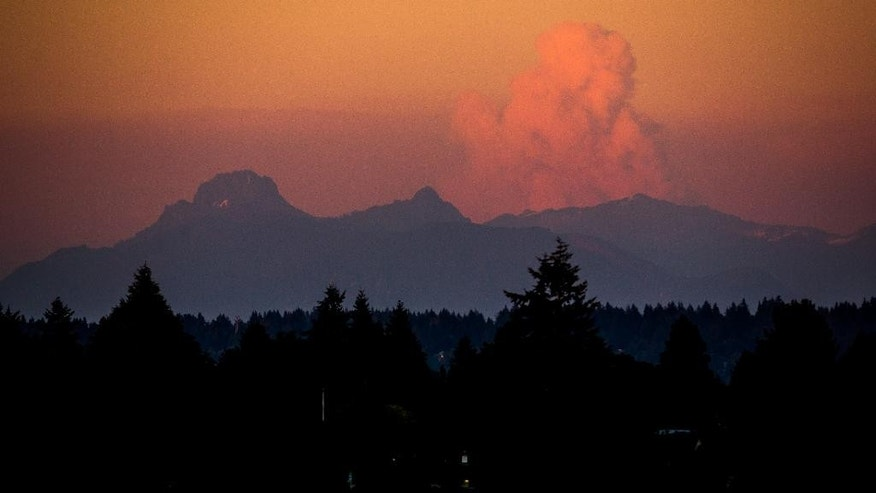 CORRECTS BYLINE TO JOSHUA BESSEX - A large cloud rises over wildfires in Eastern Washington as seen from University District at sunset on Wednesday, July 16, 2014, in Seattle, Wash. Worsening wildfire activity has prompted the governor's offices in both Washington and Oregon to declare a state of emergency, a move that enables state officials to call up the National Guard. In Washington, that declaration covers 30 eastern Washington counties. (AP Photo/seattlepi.com, Joshua Bessex)