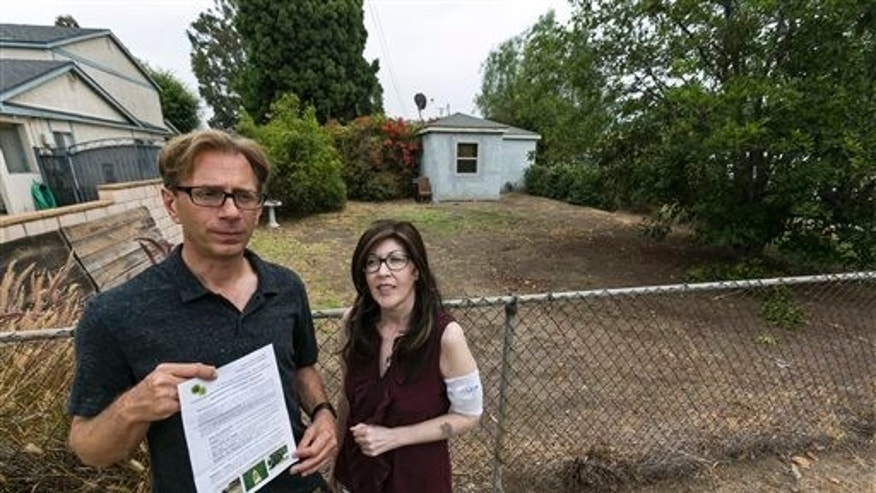 July 17: Michael Korte and his wife Laura Whitney, pose outside their home lawn in Glendora, Calif. The Southern California couple who scaled back watering due to drought received a letter from the city of Glendora warning that they could face fines if they don't get their brown lawn green again.