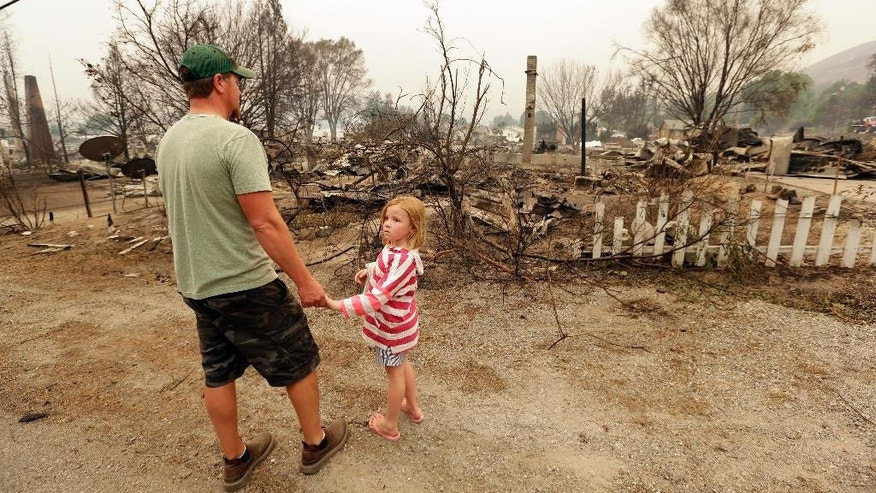 Forrest Harrison holds the hand of his daughter, Avery, 5, as he looks over the rubble remaining from his home after a wildfire destroyed it the night before Friday, July 18, 2014, in Pateros, Wash. A fire racing through rural north-central Washington destroyed about 100 homes, leaving behind smoldering rubble, solitary brick chimneys and burned-out automobiles as it blackened hundreds of square miles. Friday's dawn revealed dramatic devastation, with the Okanagan County town of Pateros, home to 650 people, hit especially hard. (AP Photo/Elaine Thompson)
