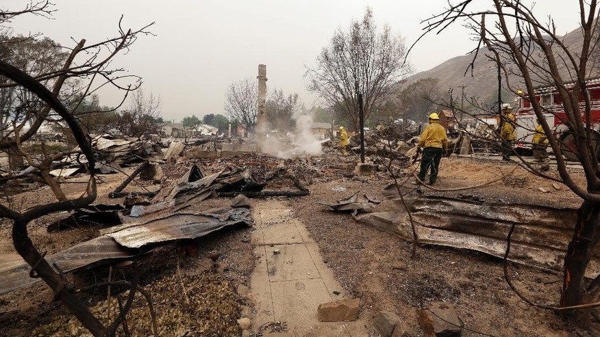 Firefighters work on the still-smoldering remains of a house destroyed the night before in a wildfire, Friday, July 18, 2014, in Pateros, Wash. A fire racing through rural north-central Washington destroyed about 100 homes, leaving behind smoldering rubble, solitary brick chimneys and burned-out automobiles as it blackened hundreds of square miles. Friday's dawn revealed dramatic devastation, with the Okanagan County town of Pateros, home to 650 people, hit especially hard. (AP Photo/Elaine Thompson)
