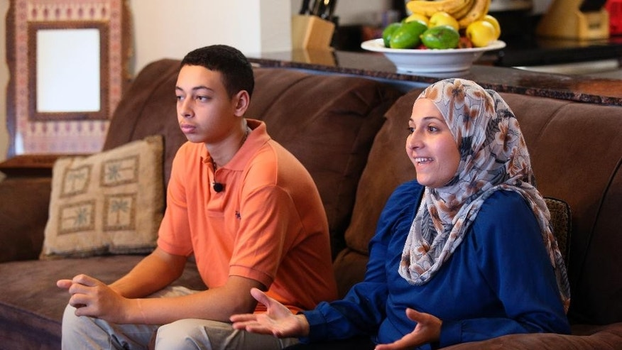 "Tariq Abu Khdeir, 15, left, sits with his mother Suha Khdeir during interview in their home, Sunday, July 20, 2014, in Tampa, Fla. Tariq Abu Khdeir flew home to Tampa last week and said in an interview Sunday with The Associated Press he hopes one day to visit loved ones anew and ""come back safe."" Israeli authorities released Tariq three days after he was detained and sentenced him to nine days of house arrest while they investigated what they said was his participation in violent protests over the death of his cousin, 16-year-old Mohammed Abu Khdeir. (AP Photo/Scott Iskowitz)"