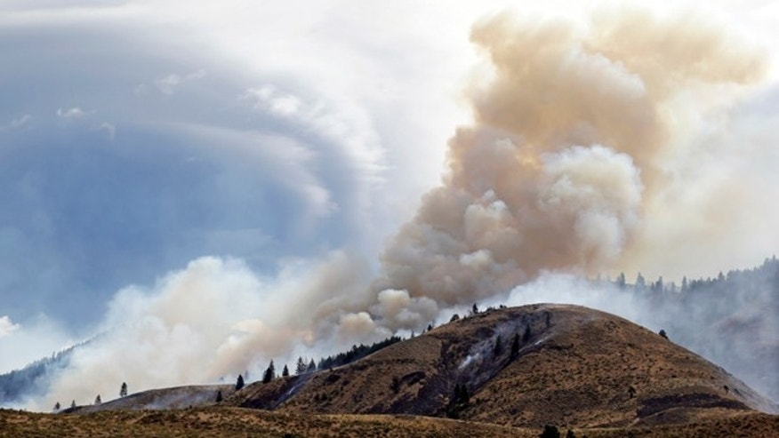 July 19, 2014: Smoke billows from a wildfire in the Methow Valley in Winthrop, Wash. A wind-driven, lightning-caused wildfire racing through rural north-central Washington destroyed about 100 homes Thursday and Friday, leaving behind solitary brick chimneys and burned-out automobiles as it blackened hundreds of square miles in the scenic Methow Valley northeast of Seattle. (AP Photo/Elaine Thompson)