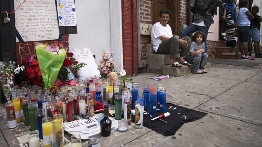 July 19, 2014: Pedestrians sit near a memorial for Eric Garner erected near the site of his death. (AP Photo/John Minchillo)