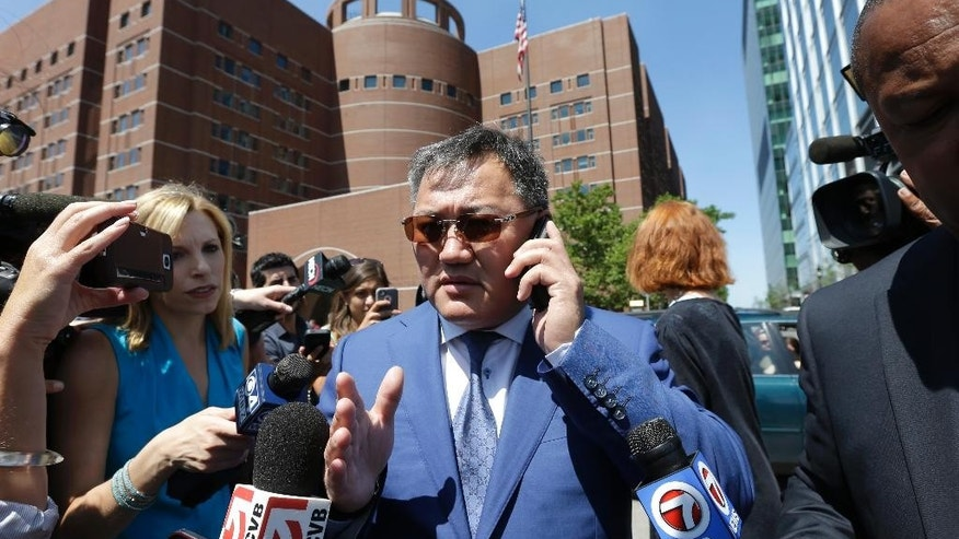 Amir Ismagulov, of Kazakhstan, center, is surrounded by members of the media as he departs federal court Monday, July 21, 2014, in Boston, where his son Azamat Tazhayakov was convicted of impeding the investigation into the Boston Marathon bombing. Tazhayakov's trial was the first stemming from the 2013 bombings, which killed three and injured more than 260 near the marathon's finish line. (AP Photo/Steven Senne)