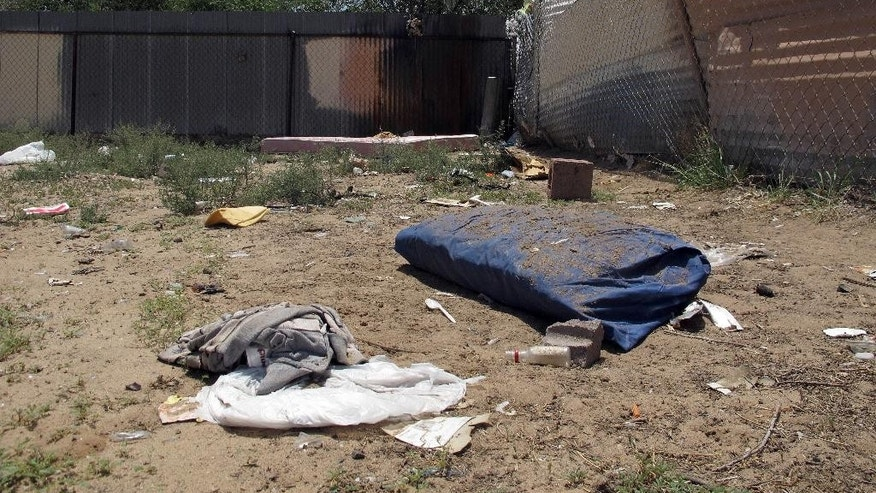 Bedding, clothing and broken glass litter a homeless encampment in Albuquerque, Monday, July 21, 2014, where three teenagers are accused of fatally beating two homeless men. The teens, aged 15, 16 and 18, have been charged with open counts of murder in the Friday night killings. (AP Photo/Jeri Clausing)