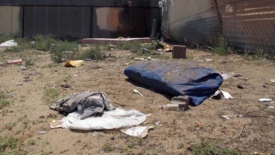 July 21, 2014: Bedding, clothing and broken glass litter a homeless encampment in Albuquerque where three teenagers are accused of fatally beating two homeless men. The teens, aged 15, 16 and 18, have been charged with open counts of murder in the Friday night killings. (AP Photo/Jeri Clausing)