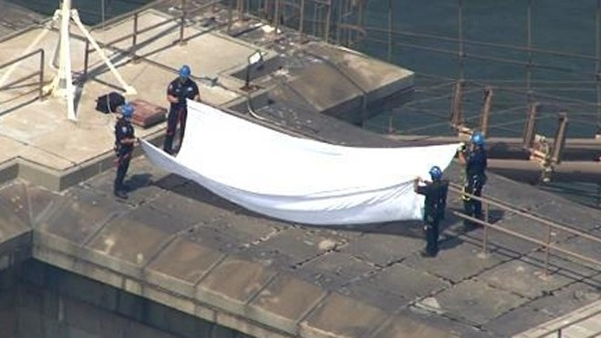 Police officers fold one of two white flags found on top of the Brooklyn Bridge late Tuesday morning.