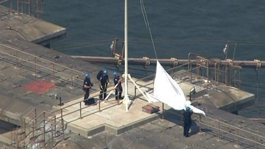 Police offers lower the white flag found on them Brooklyn Bridge.