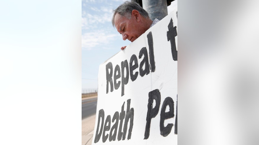 Robert Hungerford, of Phoenix, prays as he and a group of about a dozen death penalty opponents protest the possible execution of Joseph Rudolph Wood at the state prison in Florence, Ariz. on Wednesday, July 23, 2014. Arizona's highest court on Wednesday temporarily halted the execution of the condemned inmate so it could consider a last-minute appeal. The Arizona Supreme Court said it would consider whether he received inadequate legal representation at his sentencing. The appeal also challenges the secrecy of the lethal injection process and the drugs that are used. (AP Photo)
