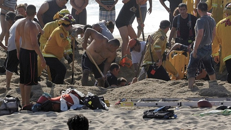 July 21: photo released by the Half Moon Bay Review shows emergency crew workers and volunteers working to rescue a man at Francis State Beach in Half Moon Bay, Calif. Authorities say a young man has died after a hole he dug on a Northern California beach collapsed and trapped him in the sand for at least five minutes.