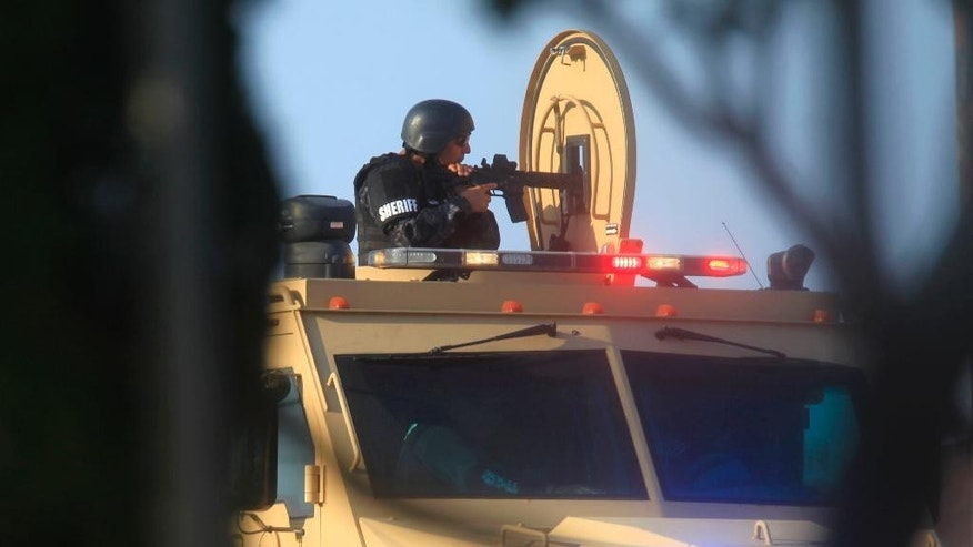 A Hidalgo County Sheriff points a rifle from the top of an armored vehicle Tuesday during a standoff with a capitol murder suspect in La Joya, Texas on Tuesday, July 22, 2014. Officials said the suspect was later presumed dead after a final assault on the house. (AP Photo/The Monitor, Nathan Lambrecht)  MAGS OUT; TV OUT