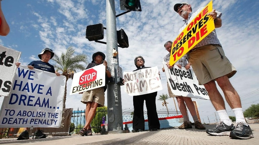 John Zemblidge, right, of Phoenix, leads a group of about a dozen death penalty opponents in prayer as they protest the possible execution of Joseph Rudolph Wood at the state prison in Florence, Ariz. on Wednesday, July 23, 2014. Arizona's highest court on Wednesday temporarily halted the execution of the condemned inmate so it could consider a last-minute appeal. The Arizona Supreme Court said it would consider whether he received inadequate legal representation at his sentencing. The appeal also challenges the secrecy of the lethal injection process and the drugs that are used. (AP Photo)