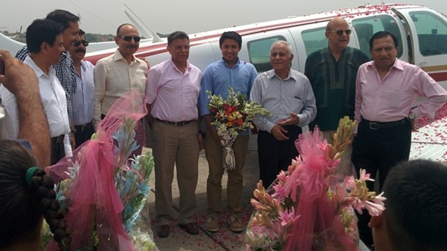 JULY 2014: Haris Suleman, center right, in blue shirt, and his father, Babar Suleman, center left, stand with the plane in early July 2014 in Pakistan that they were flying on an around-the-world trip.