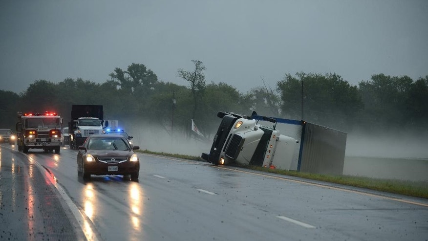 A tractor trailer truck lies on its side in the median of U.S. Route 13 in Cheriton, Va. while a fire engine responds to a nearby campground after a severe storm passed through the area, Thursday, July 24, 2014. (AP Photo/Eastern Shore News, Jay Diem)  NO SALES