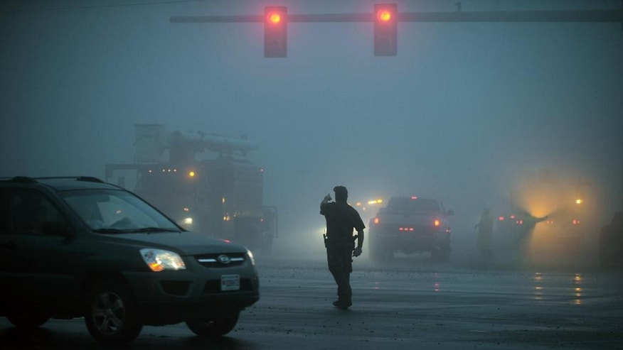 ADDS DATE - A Northampton Sheriff's Deputy directs traffic in the middle of an intersection of U.S. Route 13 in Cheriton, Va. after a severe storm passed through the area, Thursday, July 24, 2014. (AP Photo/Eastern Shore News, Jay Diem) NO SALES