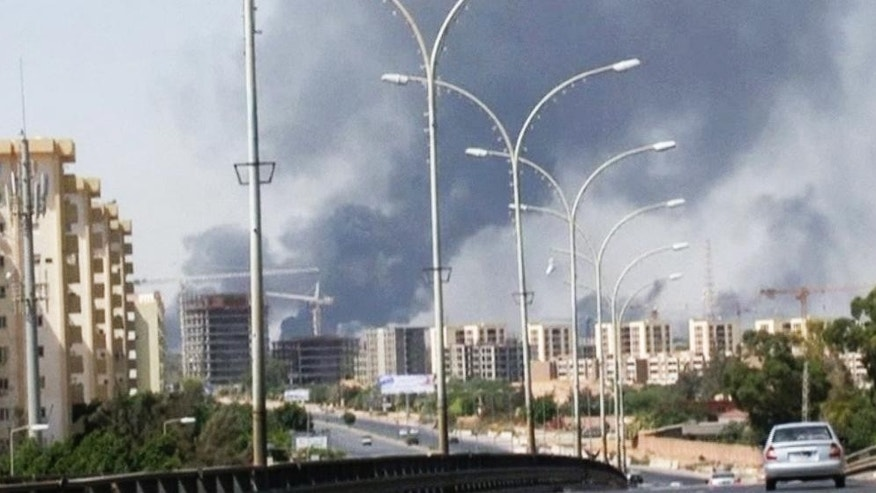 FILE - In this Sunday, July 13, 2014 file image made from video by The Associated Press, smoke rises from the direction of Tripoli airport in Tripoli, Libya. The United States shut down its embassy in Libya on Saturday, July 26, 2014, and evacuated its diplomats to neighboring Tunisia under U.S. military escort amid a significant deterioration in security in Tripoli as fighting intensified between rival militias, the State Department said.  (AP Photo/File)