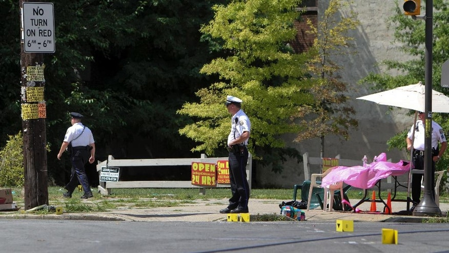 Investigators gather at the scene of a fatal accident in North Philadelphia, Friday July 25, 2014. Two children were killed and three people critically injured when a hijacked car lost control and hit a group of people near a fruit stand, according to police. (AP Photo/ Joseph Kaczmarek)