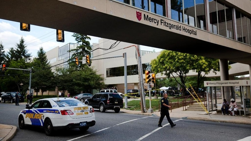 An officer walks near the scene of a shooting Thursday, July 24, 2014, at Mercy Fitzgerald Hospital in Darby, Pa. A shooting at a suburban Philadelphia hospital campus has killed one worker and injured two other people. (AP Photo)