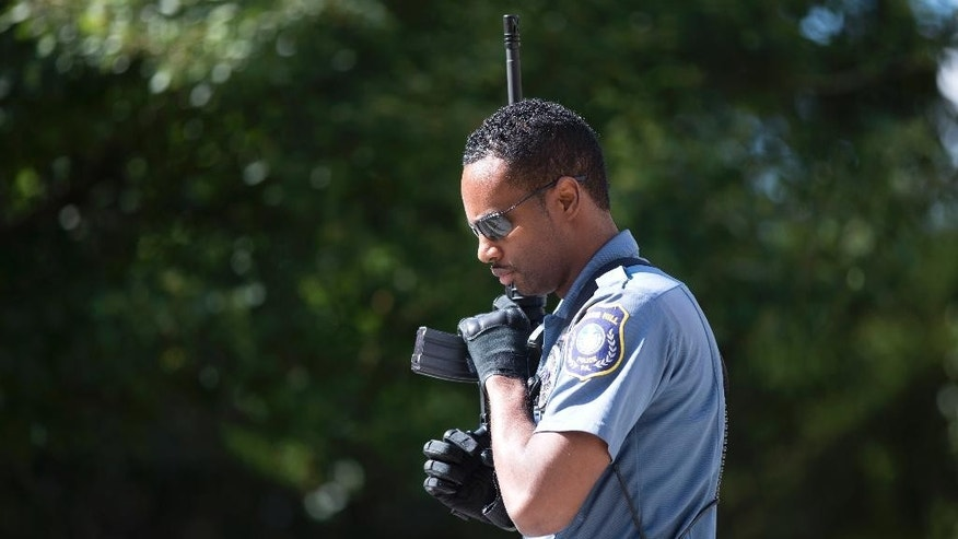 A police officer carries his weapon near the scene of a shooting at the Mercy Fitzgerald Hospital in Darby, Pa. on Thursday, July 24, 2014. A prosecutor said a gunman opened fire inside the psychiatric unit leaving one hospital employee dead and a second injured before being critically wounded himself. (AP Photo)