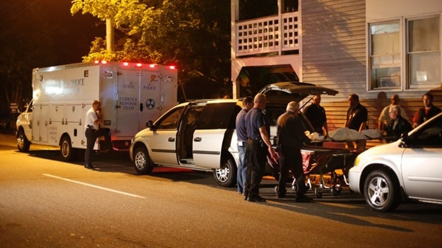 July 27, 2014: A body is moved from a crime scene at an apartment complex where five members of a family, including three children, were found dead in Saco, Maine. (AP Photo/Robert F. Bukaty)
