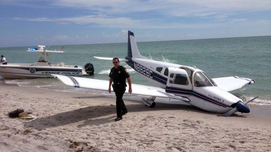 July 27, 2014: This photo provided by the Sarasota County Sheriff's Office shows emergency personnel at the scene of a small plane crash in Caspersen Beach in Venice, Fla. Authorities say a father was killed and his daughter seriously injured while walking on the sand when a small plane crash landed along Florida's Gulf Coast near Venice Beach. (AP Photo/Sarasota County Sheriff's Office)