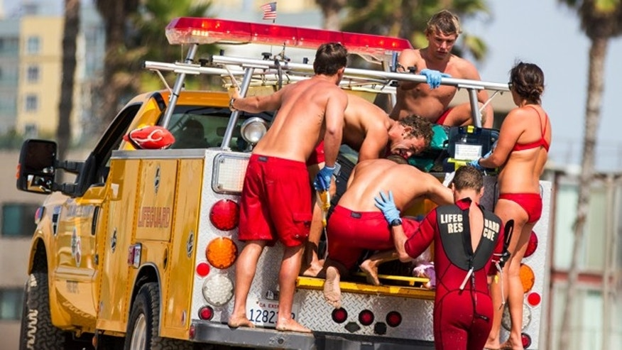 July 27, 2014: Lifeguards assist a person who was in the water and apparently struck by lightning in Los Angeles. Authorities said lightning struck 14 people, leaving two critically injured, as rare summer thunderstorms swept through Southern California on Sunday.