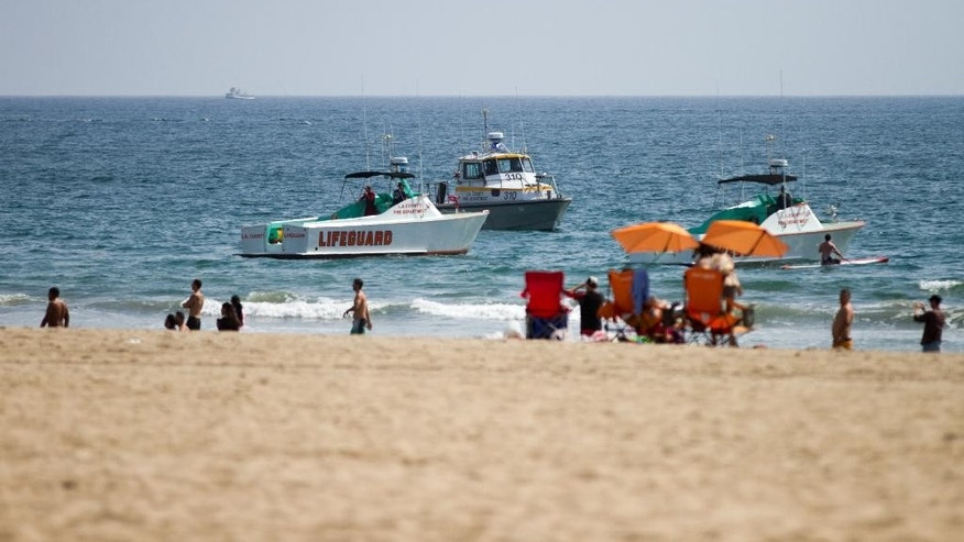 CORRECTS PHOTOGRAPHER'S NAME Lifeguard rescue boats patrol off the shore at Venice Beach, Sunday, July 27, 2014 in Los Angeles. Authorities said lightning struck 14 people, leaving two critically injured, as rare summer thunderstorms swept through Southern California on Sunday. (AP Photo/Steve Christensen)