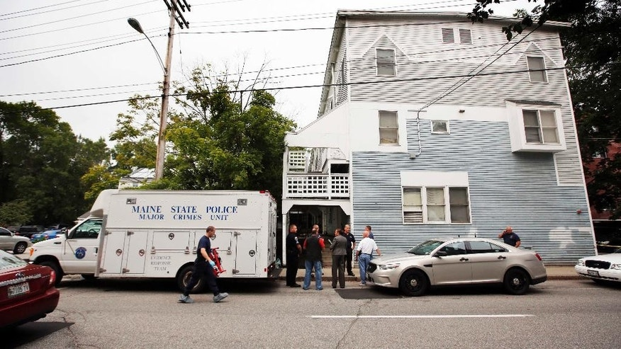 State Police investigate an apartment complex where five members of a family, including three children, were found dead Sunday, July 27, 2014, in Saco, Maine. The bodies of a father, mother and children were found inside the apartment, state police spokesman Steve McCausland said. (AP Photo/Robert F. Bukaty)