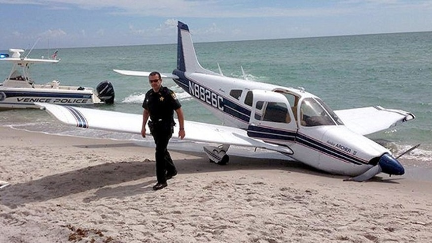 Emergency personnel examining the plane crash site at Caspersen Beach in Venice, Florida