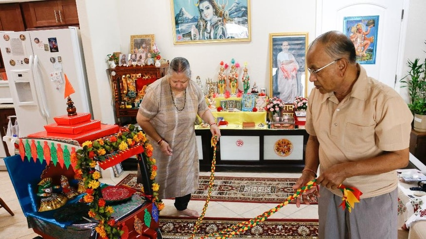 In this June 25, 2014 photo, Ranu and Arvind Patel, right, check the their 'chariot' in their home covered with religious symbols that will take part in a Hindu religious celebration at ShantiNiketan, a retirement community for people from India, in Tavares, Fla. ShantiNiketan is one of a growing number of niche retirement communities aimed at people of specific ethnic backgrounds, hobbies or collegiate allegiances. (AP Photo/John Raoux)