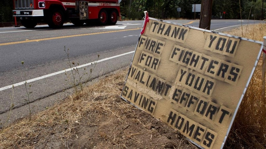 A sign on the highway thanking fire crews fighting the  Sand Fire in the rugged foothills of El Dorado county near Plymouth, Calif., on Monday, July 28, 2014, 2014. (AP Photo/Steve Yeater)