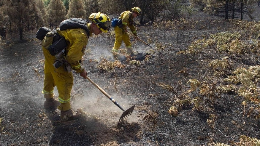 Cal Fire crew members mop up embers of the Sand Fire in the rugged foothills of El Dorado county near Plymouth, Calif., on Monday, July 28, 2014, 2014. (AP Photo/Steve Yeater)