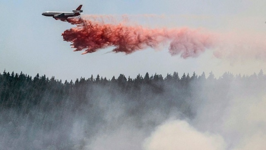 July 29, 2014: A plane drops fire retardant as firefighters battle a blaze in El Portal, Calif., near Yosemite National Park. Firefighters in the state are also battling another wildfire in the Sierra Nevada foothills east of Sacramento. (AP Photo/Al Golub)