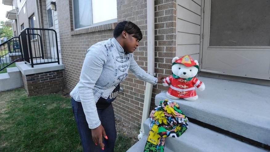Beatrice Spears leaves a stuffed animal on the front porch of a home where an 8-year-old boy was shot and killed by a bullet fired from outside that pierced the wall of his home, hitting the child in bed, early Wednesday, July 30, 2014. (AP Photo/Detroit News, David Coates)