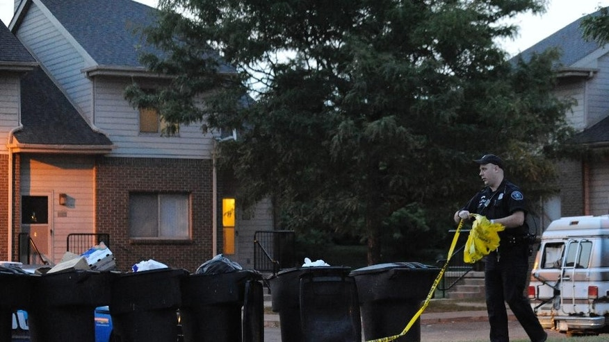 A Detroit police officer takes down the crime scene tape at the scene of a home where an 8-year-old boy was shot and killed by a bullet fired from outside that pierced the wall of his home, hitting the child in bed, early Wednesday, July 30, 2014. (AP Photo/Detroit News, David Coates)