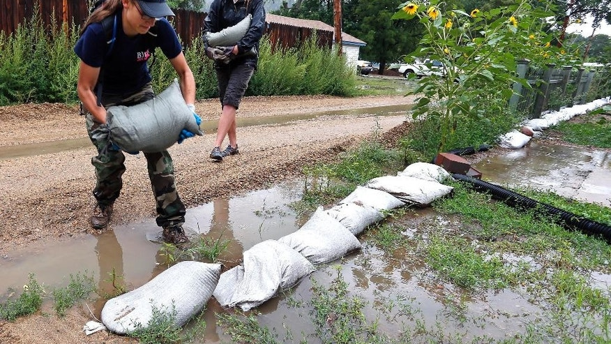 Lyons volunteer coordinators Hazel Myers, left, and Lucy Banta help sandbag a vulnerable neighborhood while steady rains fell over Lyons, Colo., which was hit hard in the previous year's flooding, July 30, 2014. High and low pressure systems, combined with summer monsoon weather, drew the abundant moisture to Colorado. More rain is forecast Wednesday. (AP Photo/Brennan Linsley)