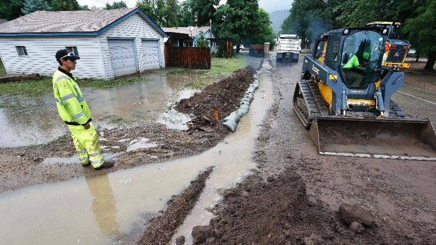 Lyons Public Works employee Keith Wittkorn, left, and his team use machinery to create flood-prevention berms in a vulnerable neighborhood while steady rains fell over Lyons, Colo., which was hit hard in the previous year's flooding, July 30, 2014. High and low pressure systems, combined with summer monsoon weather, drew the abundant moisture to Colorado. More rain is forecast Wednesday. (AP Photo/Brennan Linsley)