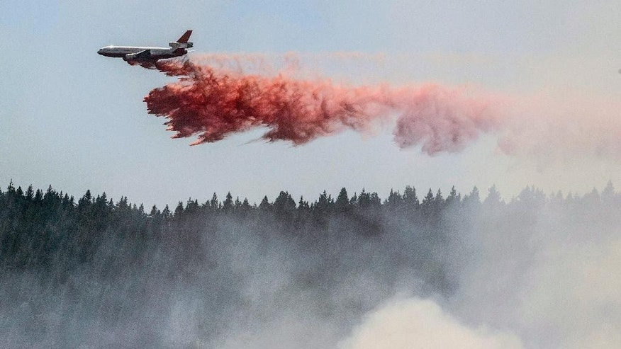 A plane drops fire retardant as firefighters battle a blaze in El Portal, Calif., near Yosemite National Park on Tuesday, July 29, 2014. Firefighters in the state are also battling another wildfire in the Sierra Nevada foothills east of Sacramento. (AP Photo/Al Golub)