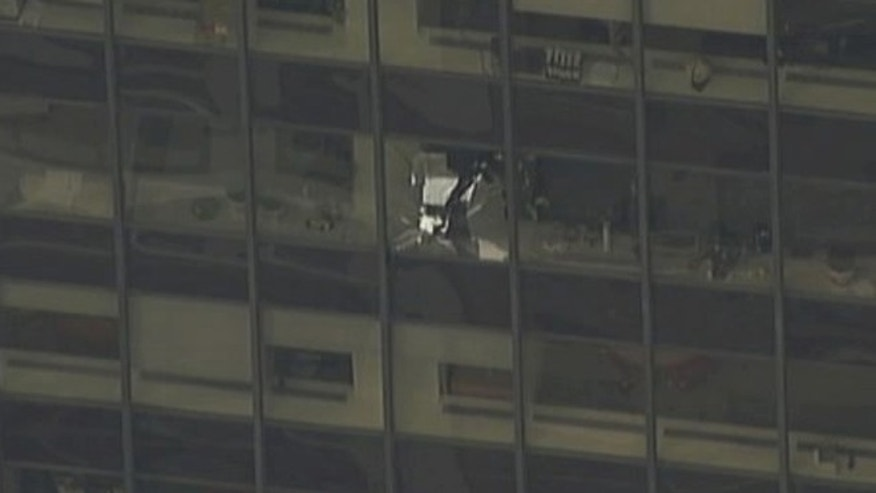 A news helicopter showed a shattered window on the NYC office building with firefighters investigating.