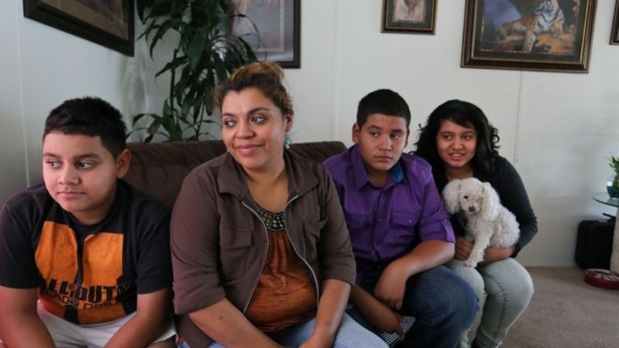 July 31, 2014: Adriana Gaytan, who came to Colorado in 1997 from the Mexican state of Zacatecas, second from left, sits at home with her children who were born in the U.S. from left to right, Osbaldo, 11, Oscar 13, Indhira, 14, and their dog Kissy, in Aurora, Colo.