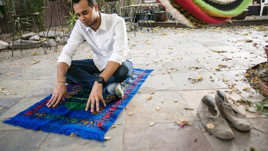 American Muslim Omar Akersim, 26, poses for a photo on his prayer rug  at his home in Los Angeles Friday, Aug. 1, 2014. Nearly 40 percent of the estimated 2.75 million Muslims in the U.S. are American-born and the number is growing, with the Muslim population skewing younger than the U.S. population at large, according to a 2011 survey by the Pew Research Center. (AP Photo/Damian Dovarganes)