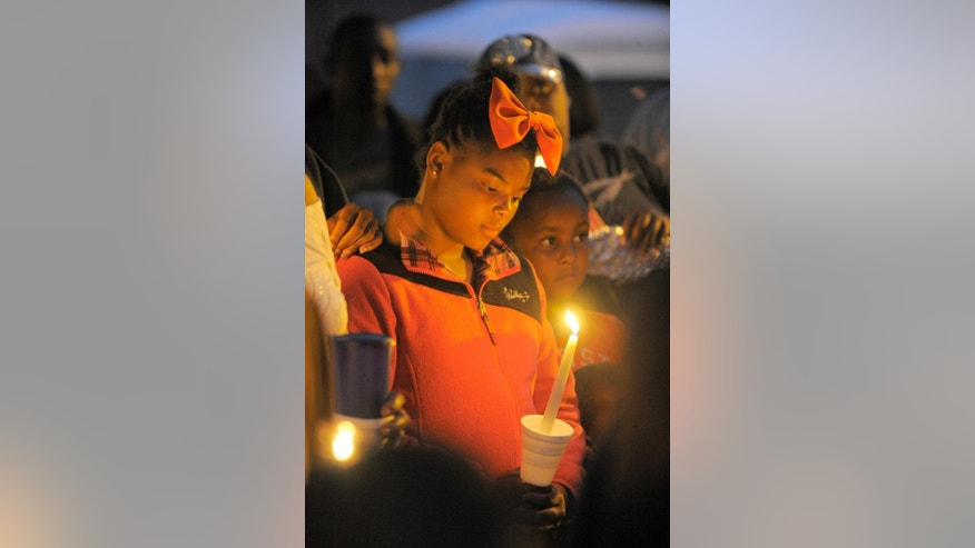 In this Wednesday, July 30, 2014 photo, Yionni Brown, 10, holds a candle during a vigil for Jakari Pearson, who died from a gunshot wound, at the New Brewster Projects in Detroit's east side. Pearson was sleeping in his upstairs bedroom when a bullet entered through a window and struck him in the chest. (AP Photo/Detroit News, Steve Perez)