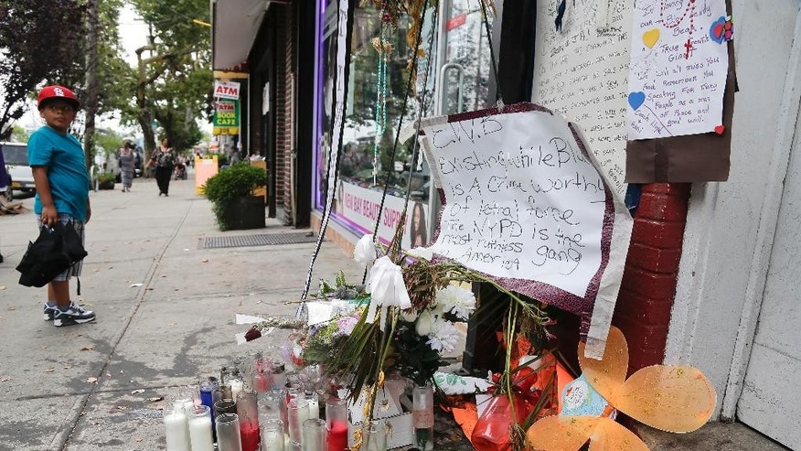 August 1, 2014: A young boy stops as he passes a makeshift memorial for Eric Garner in the Staten Island borough of New York. Garner was put in a chokehold while being arrested at the site last month for selling untaxed loose cigarettes. On Friday, the medical examiner ruled Garner's death to be a homicide caused by a police chokehold. (AP Photo/Julie Jacobson)