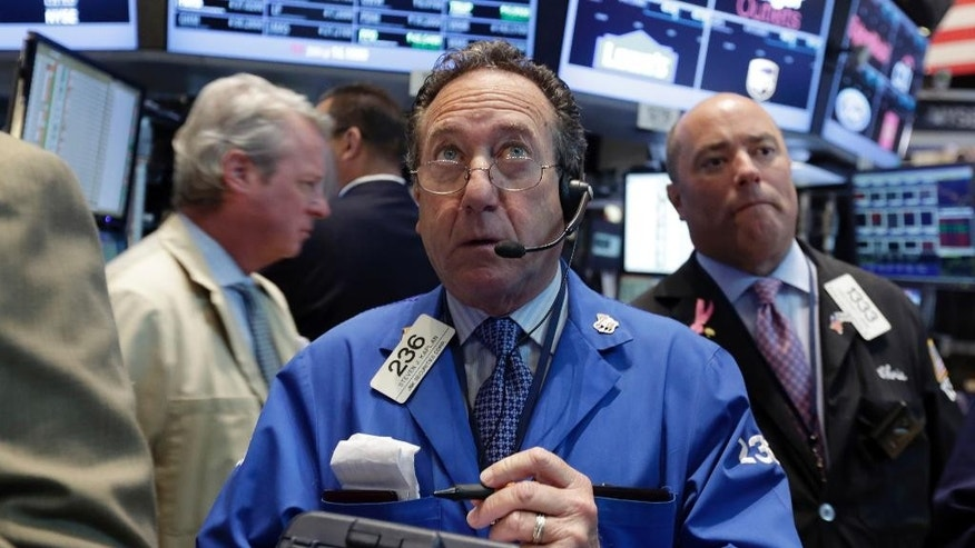 Trader Steven Kaplan, center, works on the floor of the New York Stock Exchange, Monday, Aug. 4, 2014. U.S. stocks are opening mostly higher as the market recovers from a two-day slide last week. (AP Photo/Richard Drew)