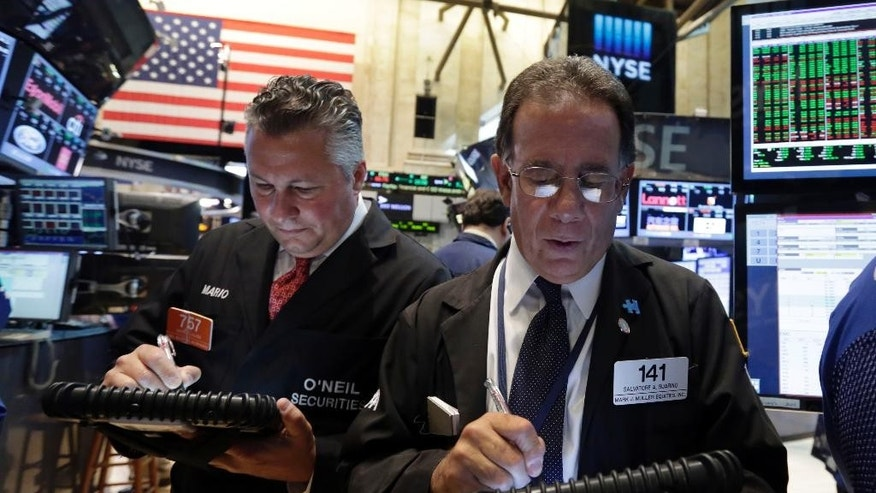 Sal Suarino, right, works with fellow traders on the floor of the New York Stock Exchange, Monday, Aug. 4, 2014. U.S. stocks are opening mostly higher as the market recovers from a two-day slide last week. (AP Photo/Richard Drew)