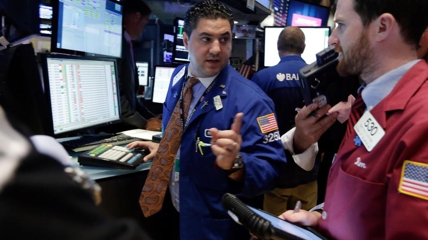 Specialist Ronnie Howard, left, works at his post on the floor of the New York Stock Exchange, Monday, Aug. 4, 2014. U.S. stocks are opening mostly higher as the market recovers from a two-day slide last week. (AP Photo/Richard Drew)