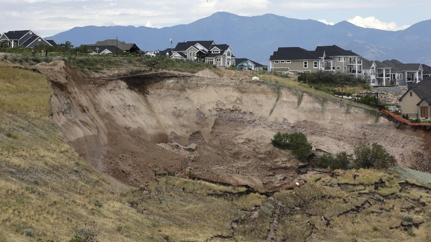 A hillside is shown following a landslide in a hillside community of North Salt Lake, Utah, Tuesday, Aug. 5, 2014. North Salt Lake officials say more than 20 homes have been evacuated following an early morning landslide that destroyed one hillside home. (AP Photo/Rick Bowmer)
