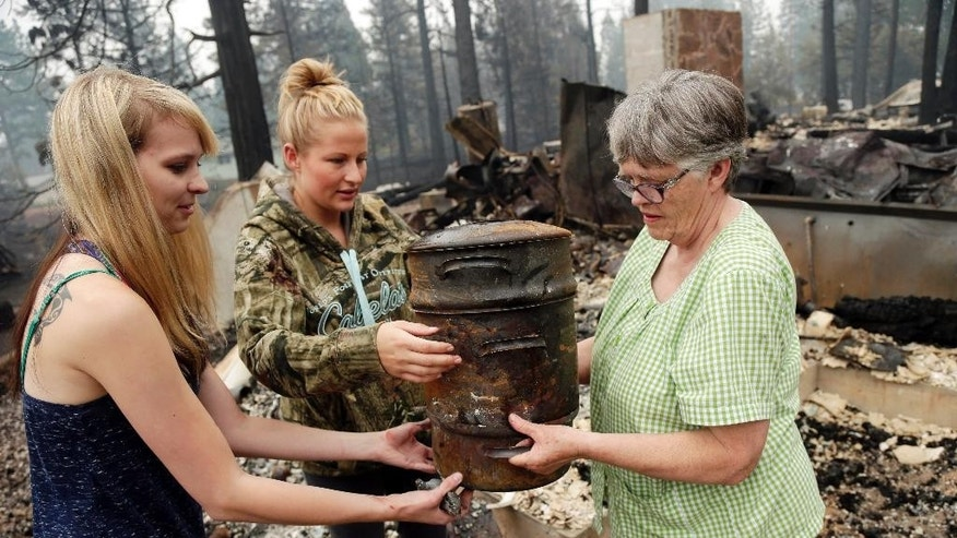 Donna Garner, right, gathers the remaining belongings left on the Fireside Village, her family's business, with the help of granddaughters Robyn Garner, center, and Amber Garner on Tuesday, Aug. 5, 2014, in Hat Creek, Calif. The Garner family business, which they owned for over 30 years, was burned down in the Eiler Fire. (AP Photo/Marcio Jose Sanchez)